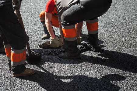 asphalting: Men at work, urban road under construction, asphalting in progress, workers install sewer manhole Stock Photo