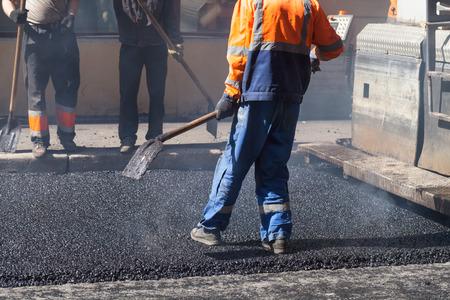 asphalting: Urban road under construction, asphalting in progress, worker with a shovel in blue and orange uniform