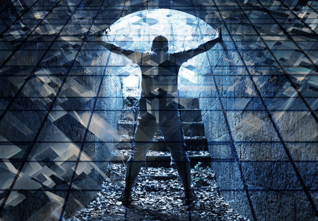 shadow man: Young man stands in dark blue tunnel with glowing end and abstract lights structure