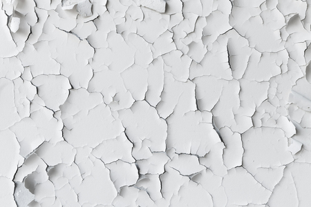 flaking: Cracked flaking white paint on the wall, background texture