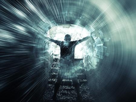 tunel: hombre joven se encuentra en el túnel azul oscuro con el extremo brillante y estructuras de luces abstractas Foto de archivo