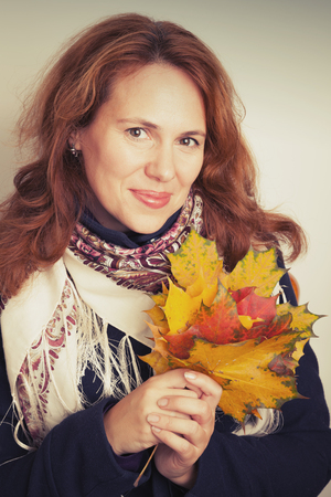 tonal: Portrait of beautiful Young Caucasian woman in traditional Russian neck scarf with colorful autumn maple leaves. Vintage tonal correction filter, retro style photo filter Stock Photo