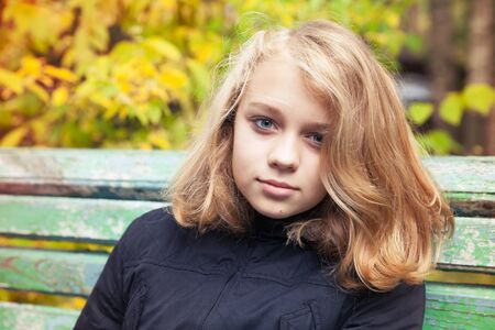 colegiala: Beautiful Caucasian blond teenage girl in black jacket sitting on old green bench in autumn park