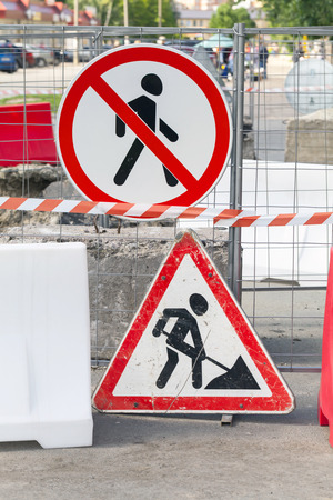 roadworks: Roadworks border with street signs on the metal fence. Road under construction, no way