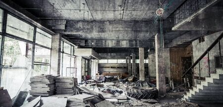 dangerous construction: Abandoned building interior. Corridor perspective with dirt and damages. Vintage tonal photo filter effect and concrete texture layer Stock Photo