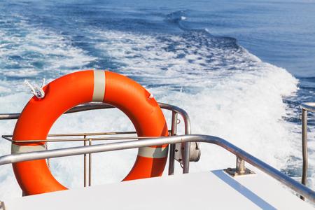 cinturon seguridad: Colgante Lifebuoy rojo en la popa del bote de rescate rápido de seguridad Foto de archivo