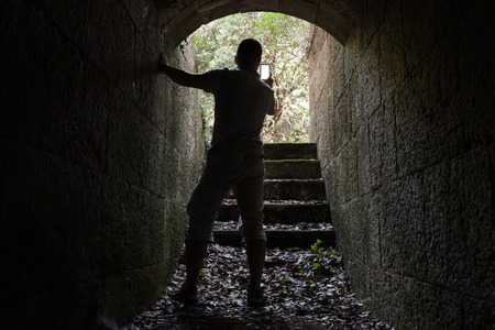 photo shooting: Young man taking photo on his mobile smart phone from dark stone tunnel Stock Photo