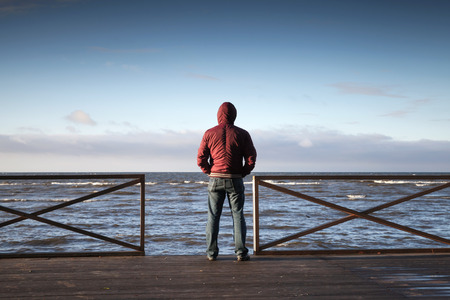 men standing: Young man in hood looking on the sea from wooden pier at morning. Rear view photo