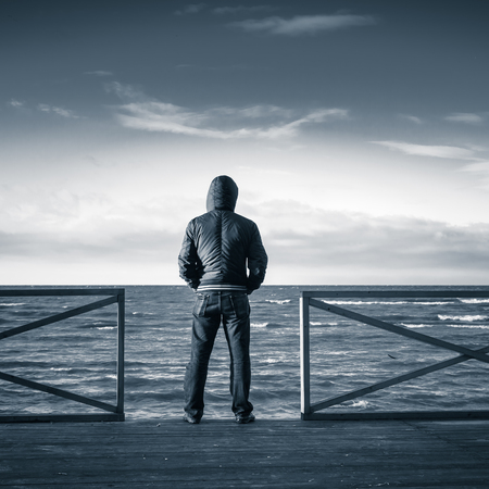 blue back: Young man looking on the sea from wooden pier. Rear view, blue toned monochrome square photo