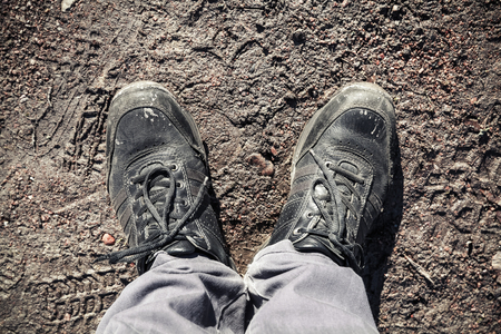 dirty feet: Male feet in dirty shoes standing on road mud Stock Photo
