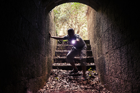 enters: Young man with a flashlight enters dark stone tunnel and looks inside with attention and fear