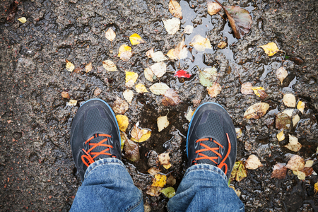 dirty feet: Male feet in sport shoes standing on dirty road with yellow falling leaves in autumn park Stock Photo