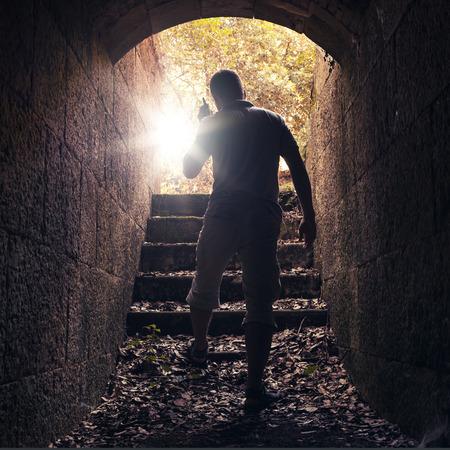 goes: Young man with radio set goes out of dark stone tunnel, warm toned photo with lens glow effect