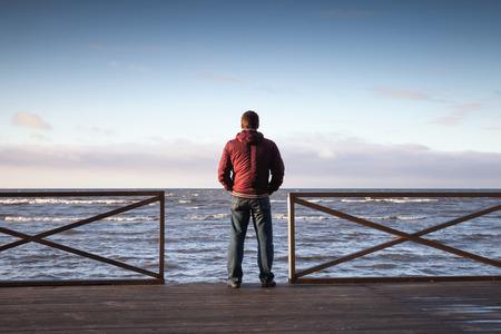 Jonge man op zoek op de zee van houten pier bij ochtend. Achter mening photo Stockfoto