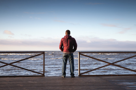 man standing alone: Young man looking on the sea from wooden pier at morning. Rear view photo