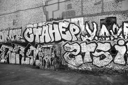 urban art: Saint-Petersburg, Russia - May 6, 2015: Street art, old urban wall with grungy graffiti text. Vasilievsky island, Central old part of St. Petersburg city. Monochrome photo