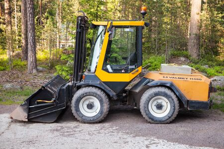 skid loader: Imatra, Finland - June 11, 2015: Yellow forklift Valmet H480 with general bucket stands on a logging area Editorial