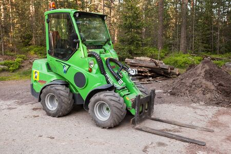 avant: Imatra, Finland - June 11, 2015: Green small forklift Avant 635 stands on a logging area Editorial