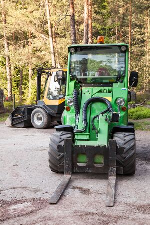 skid loader: Green small forklift stands on a logging area in forest, vertical photo