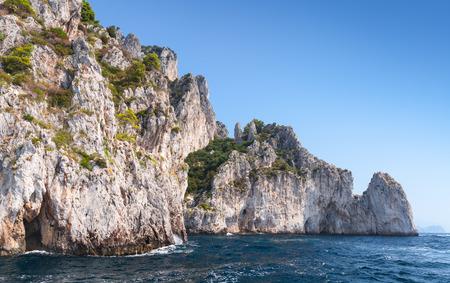 enters: Small touristic motorboat enters near the grotto in coastal rocks of Capri island, Italy Stock Photo