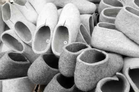 valenki: Pile of gray traditional felt slippers on the Finnish fair