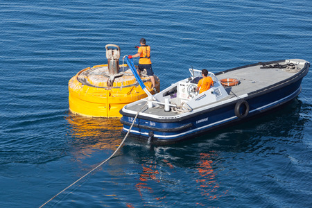 Ajaccio, France - June 30, 2015: Port operations, men at work. Motorboat is used for rope attachment on yellow mooring buoy