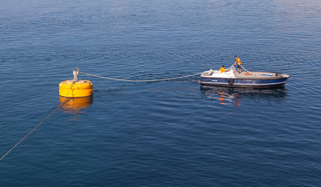 Ajaccio, France - June 30, 2015: Port operations, men at work, small boat is used for rope attachment on big yellow mooring buoy Editorial