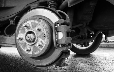 replacing: Replacing wheel on a car, close-up monochrome photo of rotor disk with brake