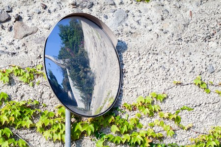 metal pole: Round mirror on metal pole near crossing streets for safety