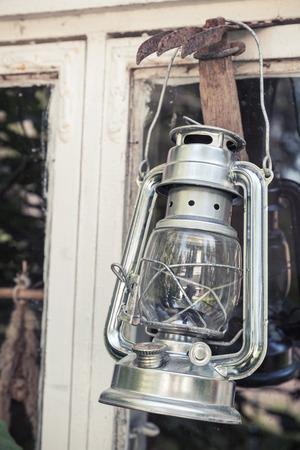 kerosene lamp: Shining metal kerosene lamp hangs on white wooden frame in Finland, vintage toned photo with old style filter effect