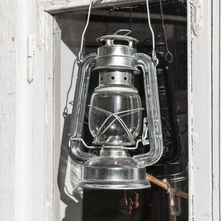 kerosene lamp: Shining metal kerosene lamp hangs on white wooden frame in Finland Stock Photo