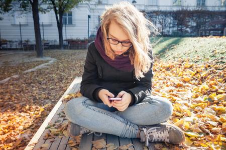 かわいい白人ジーンズと公園のベンチに座っていると、秋の屋外のポートレートのスマート フォンを使用して黒のジャケットでブロンドの十代の少