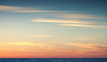 Colorful sunset sky over Atlantic ocean, natural background photo with warm tonal correction photo filter