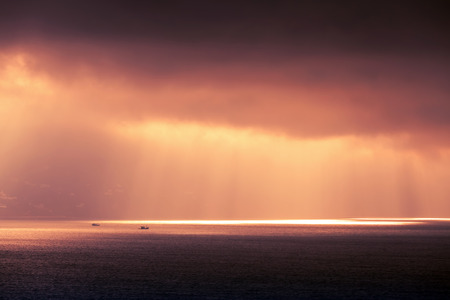 Atlantic ocean landscape, evening sunlight goes through dark cloudy sky. Purple red tonal correction photo filter effect