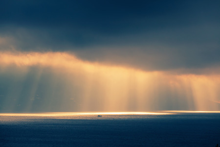 ourdoor: Atlantic ocean landscape, evening sunlight goes through dark cloudy sky. Retro style, colorful tonal correction photo filter effect