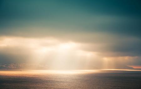 Atlantic ocean landscape, evening sunlight goes through dark cloudy sky. Retro style, colorful tonal correction photo filter effect