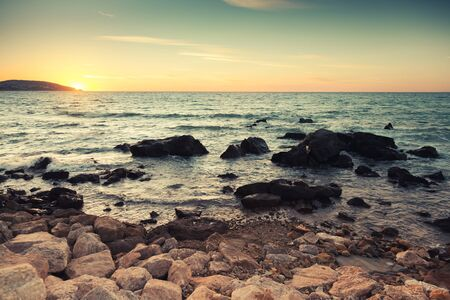 ourdoor: Coastal stones and sea water at sunset on the Atlantic ocean coast in Morocco, Tangier. Retro tonal correction photo filter effect Stock Photo