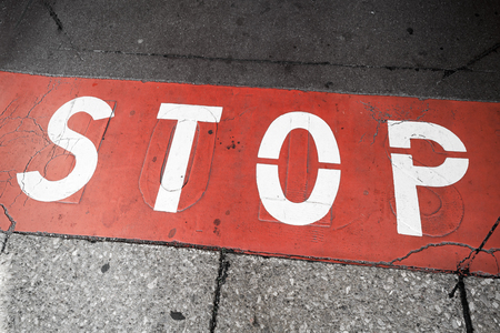 red sign: Road marking with stop label over red line on urban pavement Stock Photo