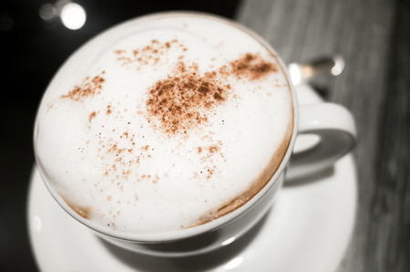 cappuccino cup: Cappuccino, cup of coffee with milk foam and cinnamon stands on black table in cafeteria, close up photo with selective focus Stock Photo