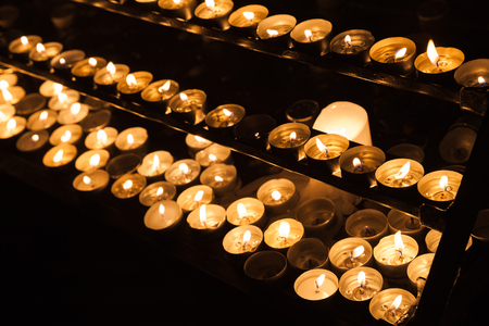 church group: Large group of small candles burning on shelves in dark catholic church Stock Photo