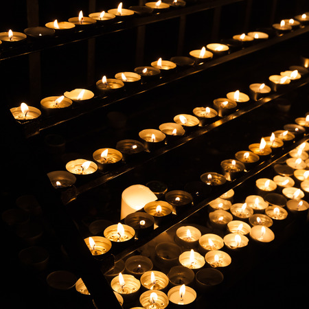 candlelight memorial: Small candles burning on shelves in dark catholic church
