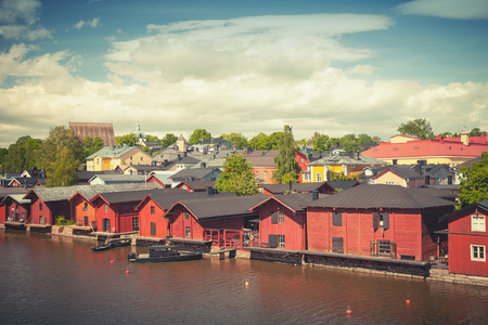 tonal: Old red wooden houses on river coast. Porvoo, small historical town in Finland. Vintage tonal correction photo filter effect Stock Photo