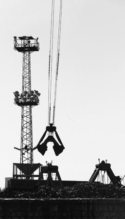 grapple: Cargo port fragment with industrial constructions and grapple loader on ropes, vertical monochrome photo