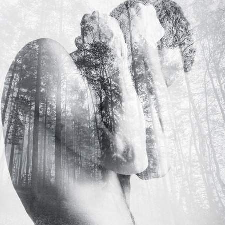blocking: Strong young man hides behind his blocking hands, double exposure photo combined with wild forest landscape Stock Photo