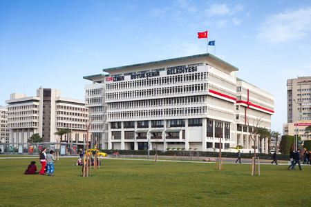 municipality: Izmir, Turkey - February 7, 2015: Izmir Metropolitan Municipality office building, ordinary people are relaxing on the grass