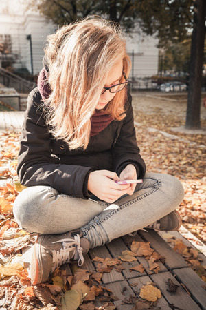 social communication: Cute Caucasian blond teenage girl in jeans and black jacket sitting on wooden park bench and using smartphone, outdoor autumn portrait, vintage style tonal correction photo filter Stock Photo