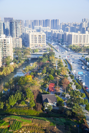 garden city: Hangzhou, China - December 5, 2014: Vertical cityscape of Hangzhou city, small green garden between big street and modern living houses