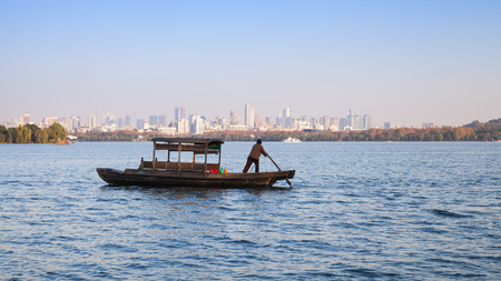 boatman: Hangzhou, China - December 5, 2014: Traditional Chinese wooden recreation boat with boatman on the West Lake. Famous park in Hangzhou city