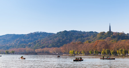 boatman: Hangzhou, China - December 5, 2014: West Lake, famous park in Hangzhou city. People float on small wooden boats Editorial