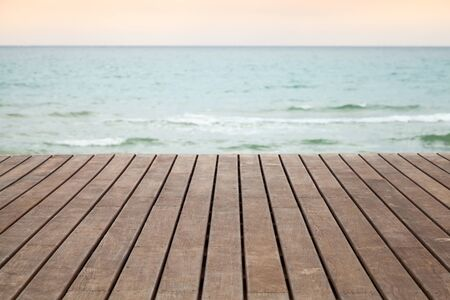 ocean floor: Wooden pier perspective with blue sea and pink sky on a background, photo with selective focus and shallow DOF Stock Photo